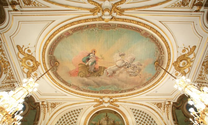 A photo of the ceiling painting in Asahi no Ma. An image of Aurora, the Roman goddess of dawn, is visible with the morning sun at her back, gallantly riding a chariot drawn by a white horse through a rift in the clouds.