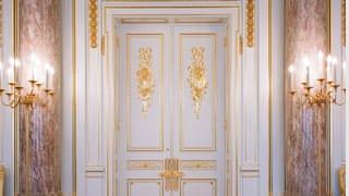 朝日廳的照片。廳壁處可見以淡紅底色並有白色斑紋的優美大理石製作之大圓柱。