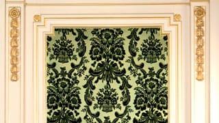 朝日の間の壁の美術織物の写真。淡い草色繻子地に濃い緑いろのビロードで「花や葉の模様が浮き出すように織り込まれている。