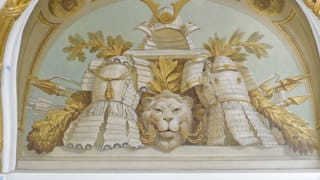 A photo of a painting near the ceiling in Asahi no Ma. A helmet and two suits of armor are depicted, and between them, a lion's head biting chains. Behind these are arrows, javelins, and lances.