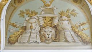 朝日の間の天井付近の天井絵画の写真。兜が一つ、鎧が2つ、その間に鎖をくわえたライオンの頭、後ろには弓矢、槍、鉾が描かれている。