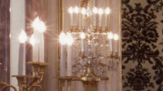朝日の間の大きな燭台の写真。金色の燭台には、鮮やかに蝋燭型の電球が光っている。