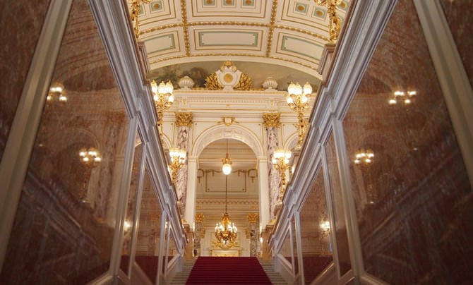 A photo of the central staircase. A red carpet has been spread over the stairs, and the walls to the left and right are made of mirror-like red marble. Straight ahead, near the ceiling, the Imperial chrysanthemum emblem can be seen.