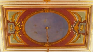 A photo of the ceiling painting in the great hall. It is laid out to appear as though one is looking up at part of a building, where the center portion represents the expansive sky, where seven doves are painted.