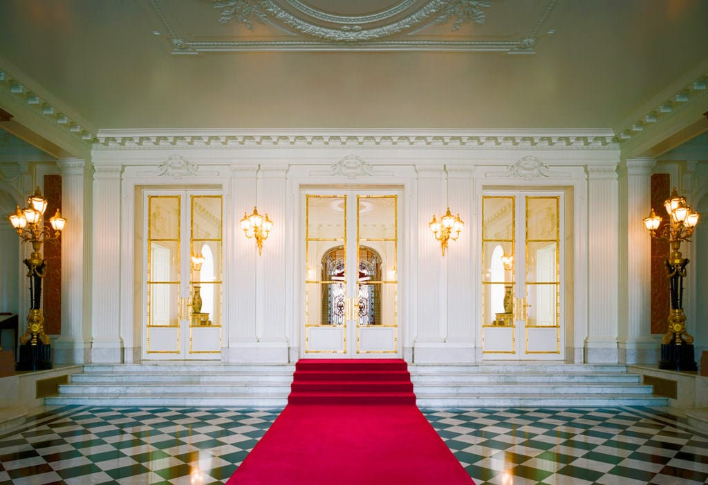 A photo of the entrance hall. The floor has a black and white checkerboard pattern, and a red carpet has been laid in its middle, extending towards the central staircase.