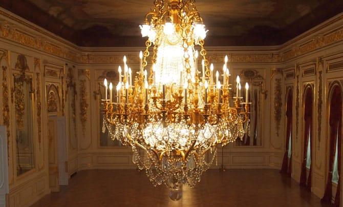 Una gran lámpara de araña hecha principalmente de cristal cuelga del techo.