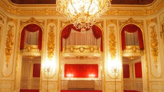 A photo of the orchestra box in Hagoromo no Ma. The orchestra box is built on a second floor within the room. It's red decorative curtains and gilded stucco relief are distinctive.