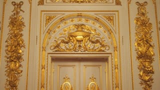 The walls near the doors are decorated with gilded stucco reliefs. A pattern of violins and other Western instruments is combined with traditional Japanese instruments, like the lute (biwa) and hand drum (tsuzumi).