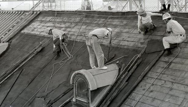 昭和43年に着工した迎賓館赤坂離宮の改修工事の様子。屋根に工事職人があがり、屋根の葺き替えの作業を行っています。