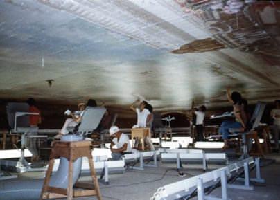 昭和43年に着工した迎賓館赤坂離宮の改修工事の写真。朝日の間の天井絵画を修復するため、天井近くまで組まれた足場ステージの上では、多くの人が椅子に座って天井を見上げながら作業を行っています。
