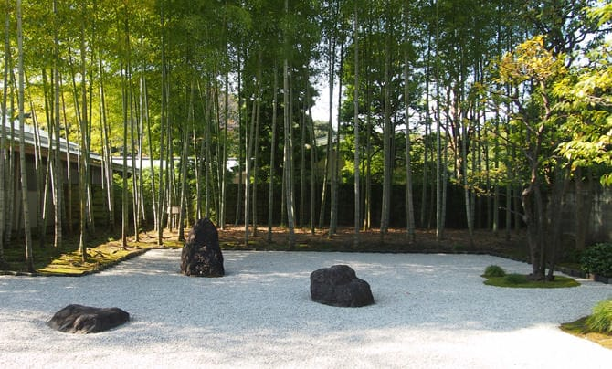 A photo of the inner garden of the Japanese Annex. Pure white pebbles blanket the ground, and three stones from Kifune, in Kyoto, have been arranged in the center. Moso bamboo grows behind the rocks.