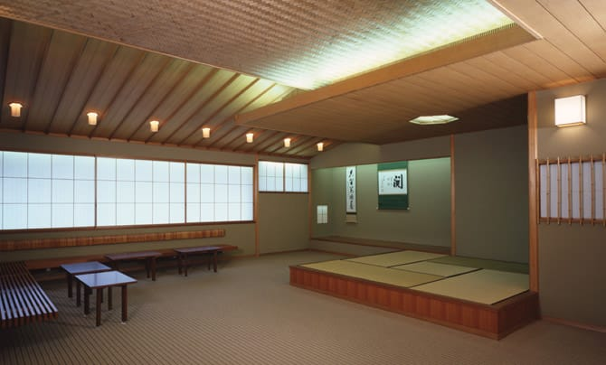 A photo of the tea room in the Japanese Annex. Several chairs have been arranged by the wall, in addition to a four-and-a-half tatami mat space. A hanging scroll is displayed in the toko-no-ma alcove in the back of the room.