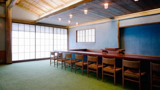 A photo of the dining chairs in the Japanese Annex. Chairs are arranged along a counter. The pillars and exposed beams of the room are made of rough-hewn chestnut, and slats of bamboo are affixed to the ceiling, creating a rustic appearance.