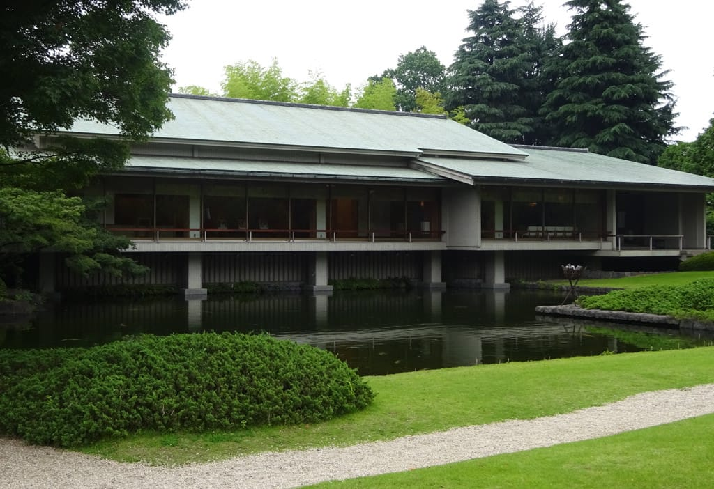 A photo of the exterior of Yushintei, the Japanese Annex. There is a path through the lawn leading to the annex. Across a pond, the gabled roof of the one-story Japanese Annex can be seen.