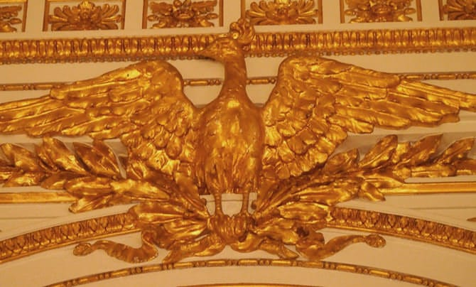 A photo of the mythical bird known as the Ran, a variety of phoenix, spreading its wings wide. It shines golden, a gilded stucco relief.