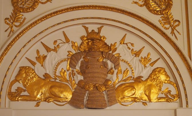 A photo of a gilded stucco relief of an armored warrior. The design is of the warrior is at center, with seated lions facing outwards on both sides.