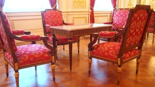 A photo of the chairs and tables in Sairan no Ma. A pattern is embroidered on the red fabric portion of the chairs.