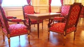 彩鸾厅的桌椅照片。椅子的布料部分为在红色质地上用银线刺绣花纹。