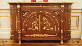 A photo of furniture in Sairan no Ma. Golden decorations have been applied to the mahogany.