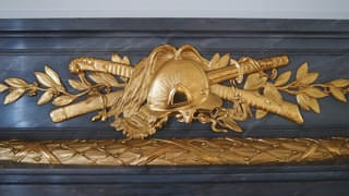 A photo of decoration on the mantlepiece in Sairan no Ma. The decoration is a design of a Western-style helmet with a Japanese katana sword and a saber behind it.