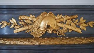 彩鸞の間のマントルピースの装飾の写真。金色の装飾は、西洋の兜の後ろに日本刀とサーベルのデザインになっています。