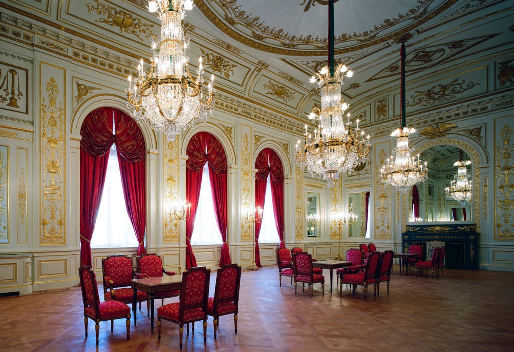 A photo of the whole of Sairan no Ma. Three chandeliers, magnificent gold-leaf plaster relief, and ornate chairs and tables are set in the room. Patterns are embroidered on the red fabric of the chairs.