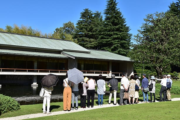 An image of visitors to the main building. In this photo, many visitors are lined up while viewing Kacho no Ma. Some visitors can also be seen viewing the room while listening to an audio guide.