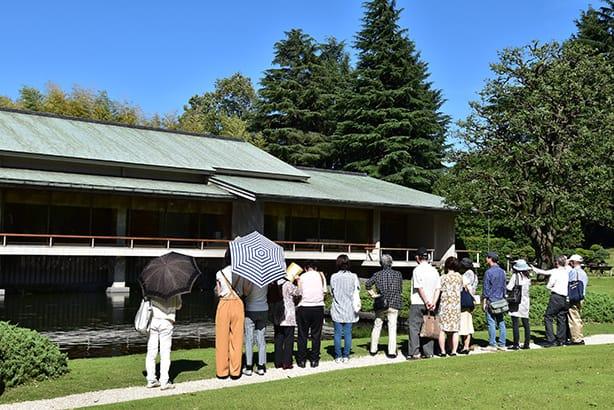 和風別館庭園的參觀景況,參觀者並排於和風別館前的池塘旁,聽著導覽員的解說。