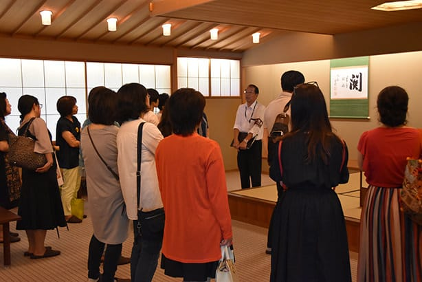 A photo of visitors in the tea room of the Japanese Style Annex, Yushintei. Visitors are listening to the explanation of the tour guide as they make their way around.
