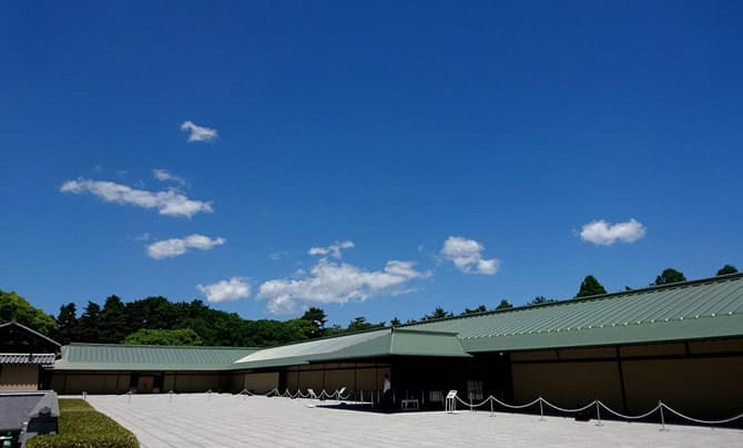 앞뜰의 끝에서 정면 현관을 대각선으로 촬영한 모습입니다. 푸른 하늘이 넓게 펼쳐져 있어 사진으로 보면 앞뜰과 건물이 매우 넓다는 것을 알 수 있습니다.