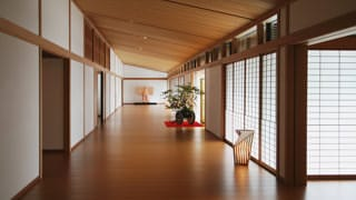 A corridor extends straight ahead. A kimono is on display at the end of the corridor, and in the middle of the corridor, before the front entrance is a flower arrangement. The flooring reflects the light from paper lanterns, and the light passing through the sliding paper doors of the hallway.