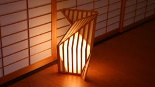 薄暗い回廊の中で、床に置かれた行灯があたたかな光を放っています。行灯のすぐ後ろには障子があります。行灯は折り紙をイメージしたデザインになっています。