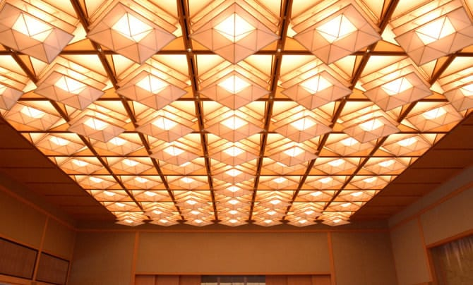 A photo of the illuminated coffered ceiling in Fuji no Ma. Rhombus-shaped lights have been installed in each delineated section of the ceiling, in shapes reminiscient of three-layered Japanese kites. Some lights extend out from the ceiling, facing downwards, and some do not extend, creating a pattern across the ceiling.