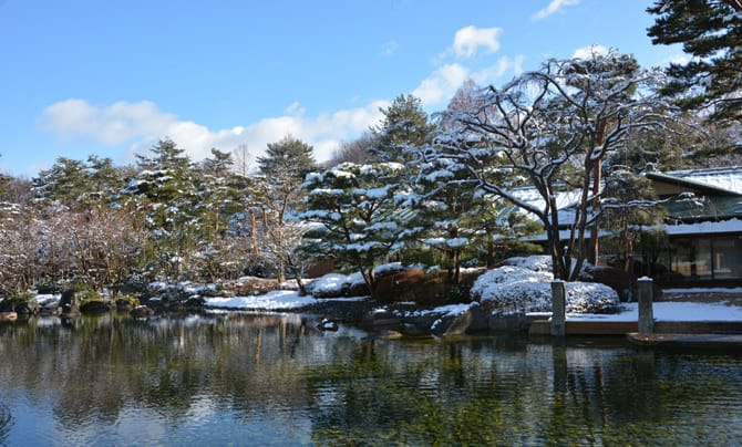 The garden in winter can be seen. Snow has piled on the trees and the roof of the building, whose image is reflected in the pond in the foreground.