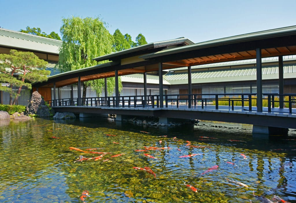 In the garden and further along the building, verdant trees grow thickly before a background of cloudless blue skies. The blue skies are reflected in the calm pond in the foreground, in which many colored carp are swimming. A broad bridge extends across the pond, connecting the eastern and western ridges of the roof of the Kyoto State Guest House.