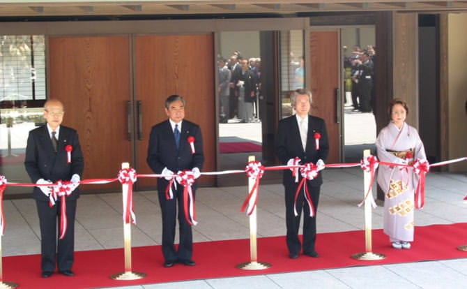 An image of the ribbon cutting at the Kyoto State Guest House Opening Ceremony. Standing before the front entrance, from left are Supreme Court Chief Justice Machida, Speaker of the House of Representatives Kono, Prime Minister Koizumi, and President of the House of Councillors Ogi at the far right dressed in kimono. A red carpet is spread beneath the four. Their scissors are in the process of slicing through the tape.