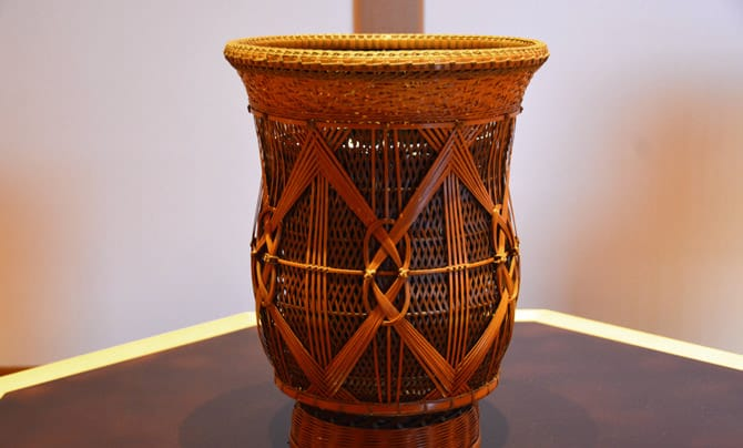 A woven flower vase is in the center of the photo. The vase's design is made with countless bamboo strips woven together. The vase is in the shape of a jar, but the top is made to open wide to accomodate flowers.