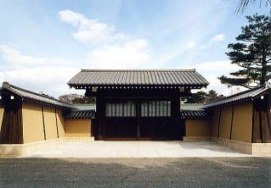 晴れた空を背景に、左右を築地塀に囲まれた京都迎賓館の正門が正面にあります。手前には京都御苑の砂利道があります。正門や、築地塀の後ろには木々が見えます。