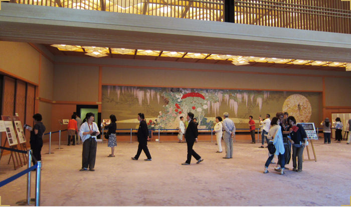 An image of a visit to the Kyoto State Guest House via guided tour. Visitors see each room in the Guest House while listening to an explanation from the tour guide.