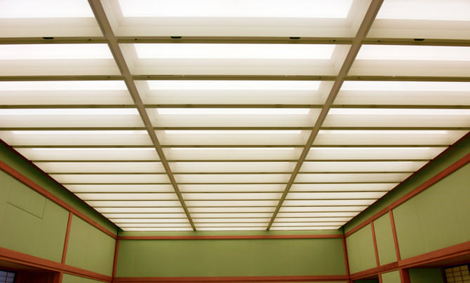 A photo of the ceiling in Yubae no Ma. The lighting is indirect, and gives off a soft light. The ceiling is divided into rectangular grids.