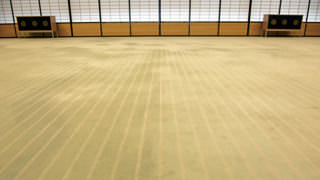 A close-up photo of the carpet in Yubae no Ma. There are white stripes in the carpet. If you look closely at these stripes, you can see bead-like shapes made to suggest the pebbles of a pond. Further examination of the pattern in the carpet reveals the shapes of white clouds floating in a pond.