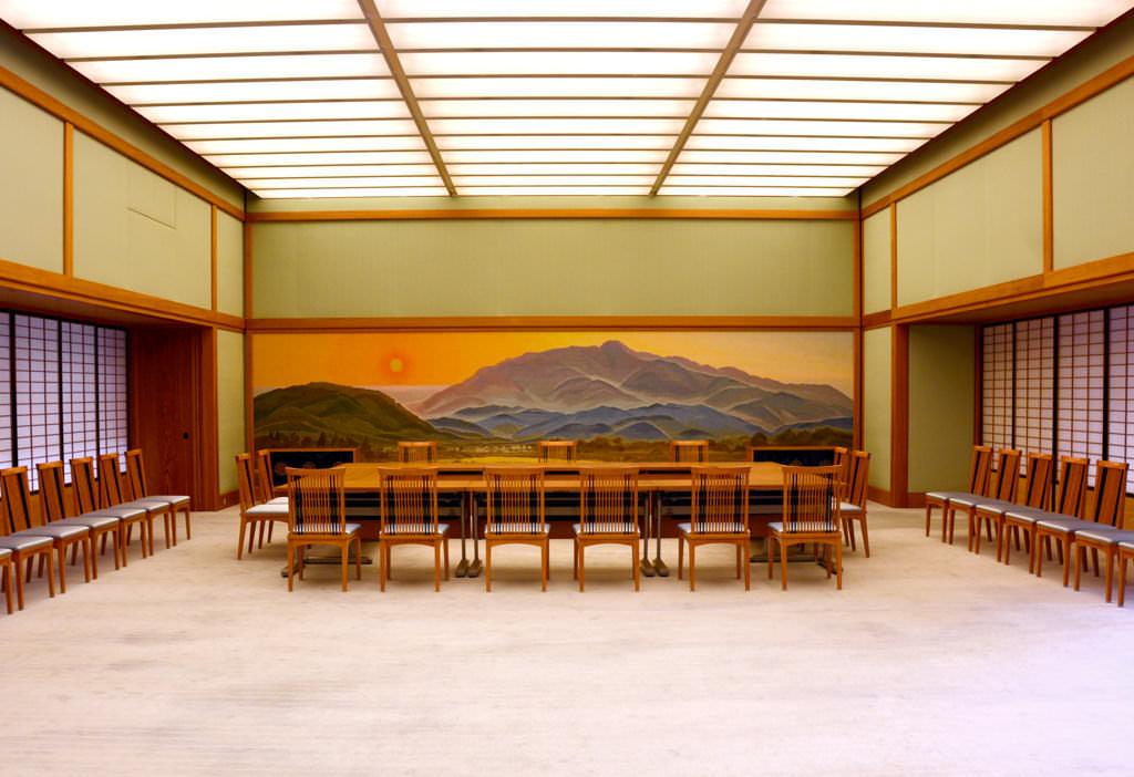 「愛宕夕照」の壁面装飾を正面奥にして撮影した、夕映の間の全体写真です。正面には四角に囲った机と椅子が置かれています。また、部屋の左右には、椅子が隙間なく並べられています。