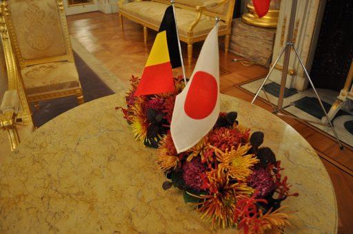 懇談会が行われる朝日の間の円卓に置かれたベルギー王国と日本国の卓上旗の写真。ベルギーの国旗をイメージした装花が添えられています。