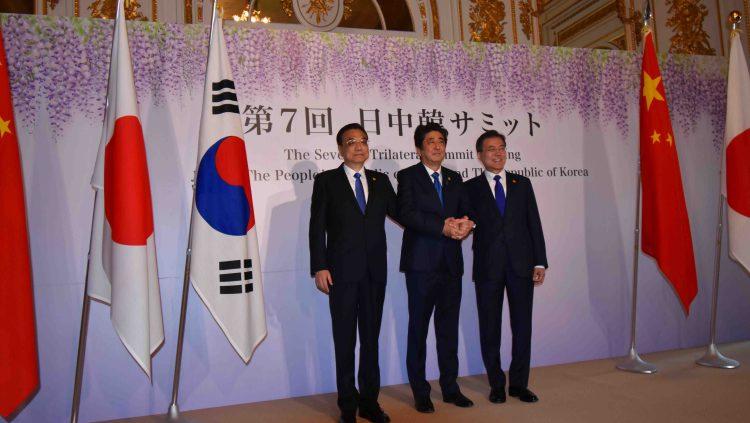 羽衣の間において、サミット前に手を携える日中韓首脳。