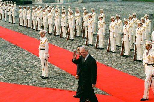 President Santer waves his hand to welcoming members, as he walks on the red carpet during the welcome ceremony in the front garden